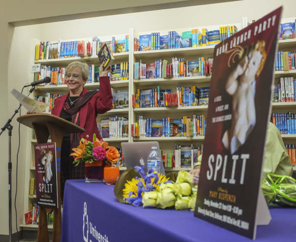Mary Dispenza holds up a copy of her memoir SPLIT: A child A priest and the Catholic Church